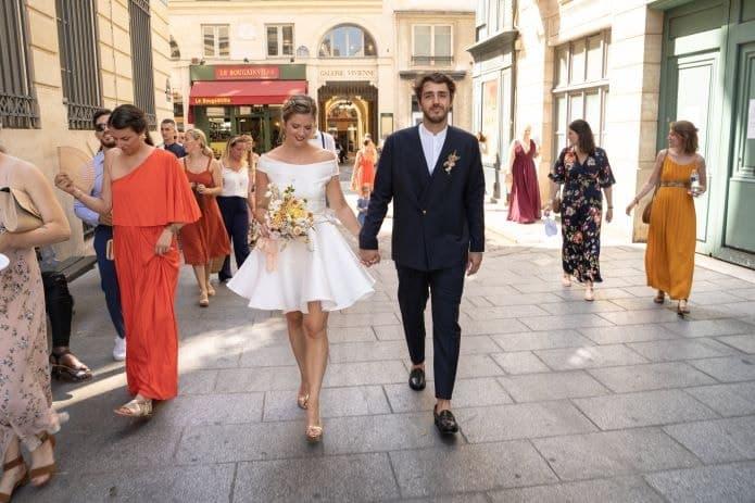 couple de mariée dans la rue avec leurs invités