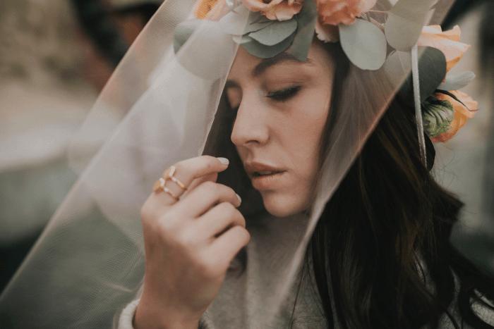 femme portant une couronne de fleurs et voile de mariée