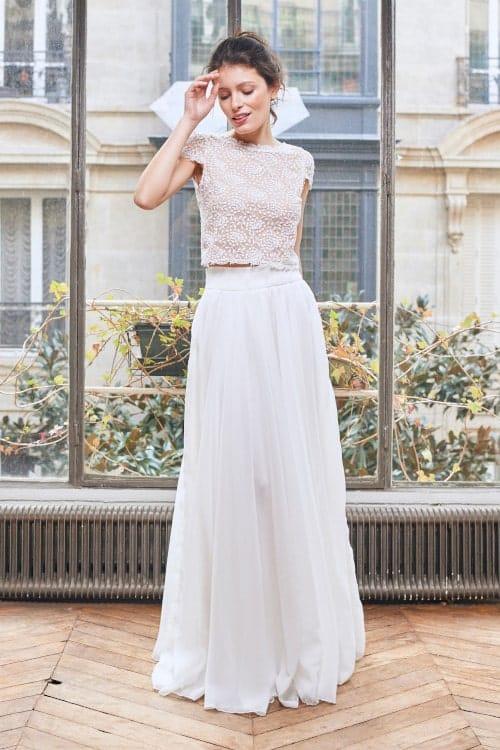 Femme portant une robe de mariée devant une fenêtre