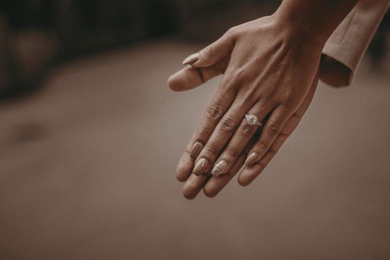 deux mains jointes et bagues de fiançailles