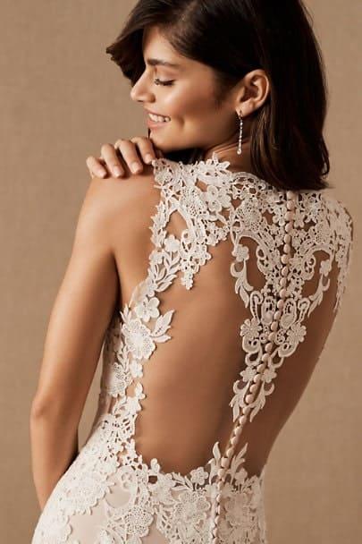 Mariée portant robe dos ouvert se tenant l'épaule