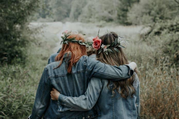 2 femmes en accolade portant veste en jean et couronnes de fleur