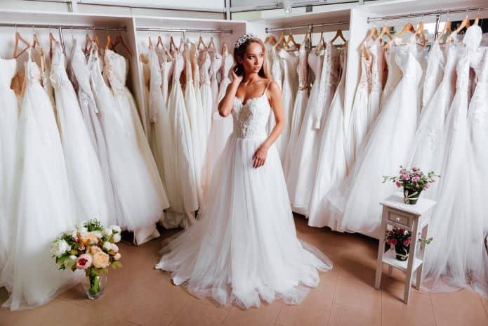 femme essayant une robe de mariée dans une boutique