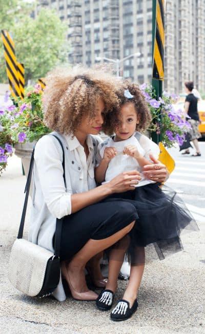 enfant sur les genoux de sa mère dans la rue