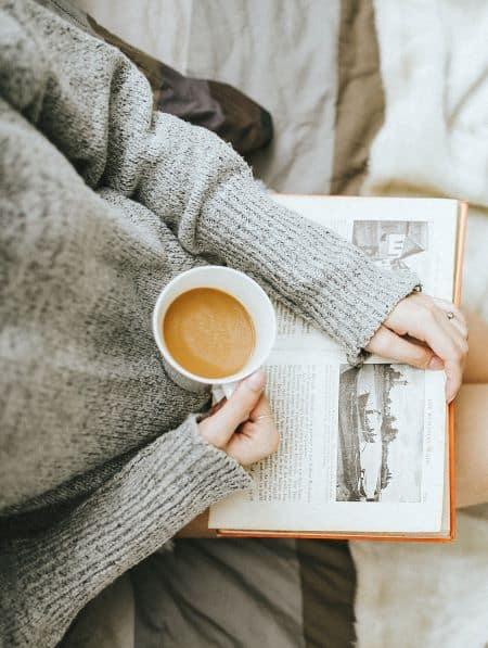 femme lisant un livre en prenant un café