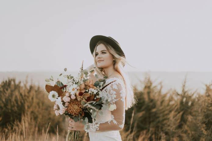 mariée portant un chapeau et un bouquet de fleurs