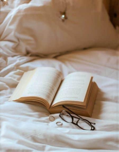 livre avec alliances pour demande en mariage sur un lit