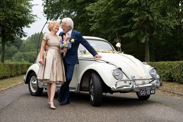 deux mariés sénior devant une voiture vintage