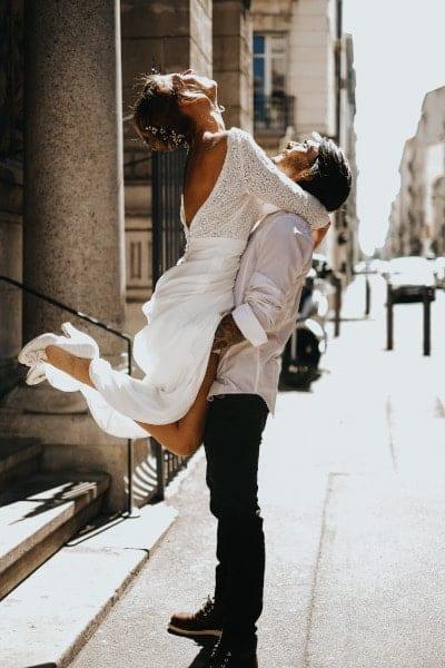 Femme portant une robe de mariée MADO sautant dans les bras d'un homme