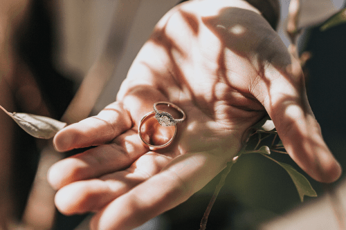 deux bagues de fiançailles dans la main d'un homme
