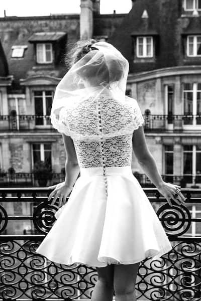 Femme de dos portant une robe de mariée courte avec voile photo en noir et blanc