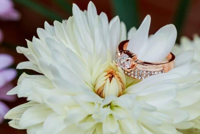 bague diamant or rose dans une fleur blanche