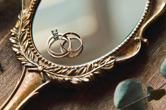 bague de fiançailles et alliance en or posées sur un miroir