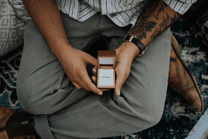 homme assis avec une bague en diamant dans les mains