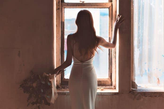 marié se tenant à la fenêtre se préparant avant le mariage
