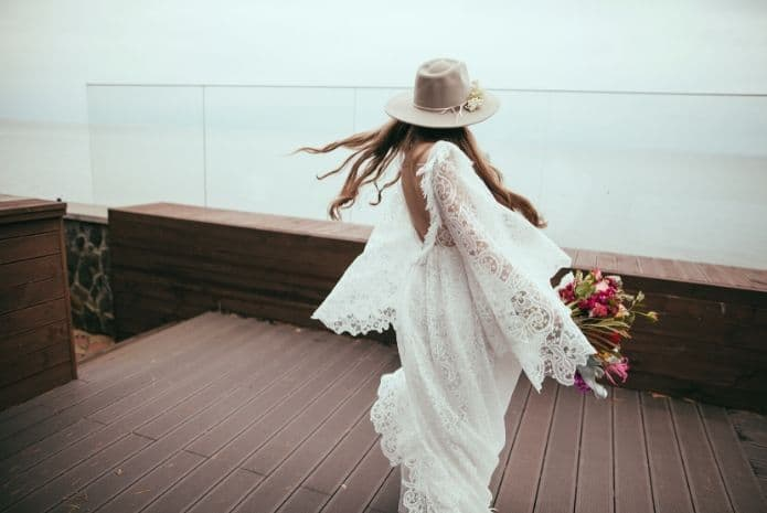 mariée portant un chapeau et robe de mariée à volant