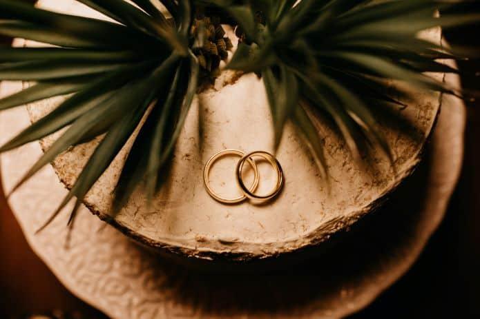 deux alliances avec gravure sur un gateau de mariage