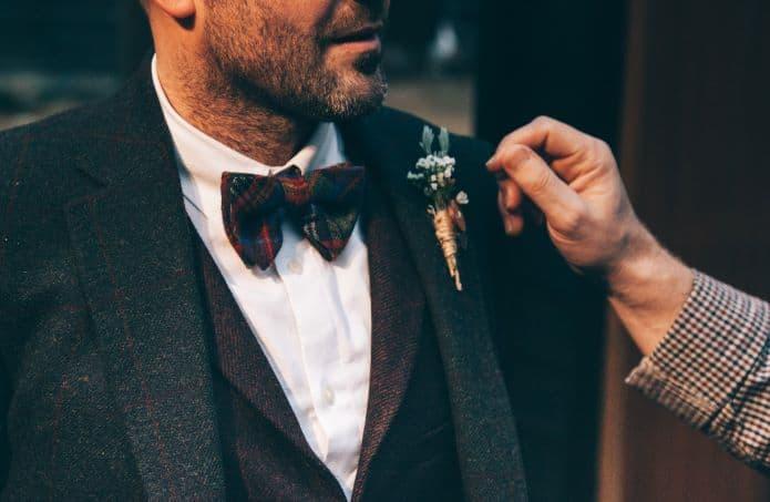 homme portant un costume en tweed et noeud papillon