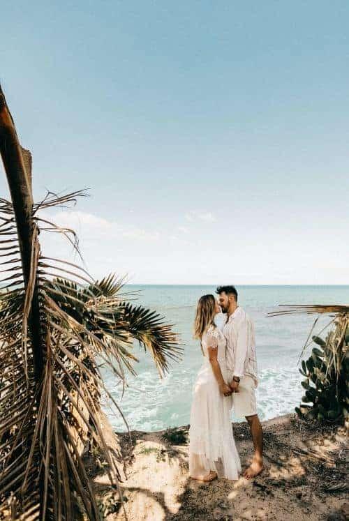 couple de mariés se tenant la main sur la plage