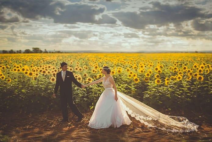 deux mariés se tenant la main dans un champs de tournesols