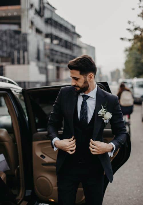 homme portant un costume de mariage noir devant voiture