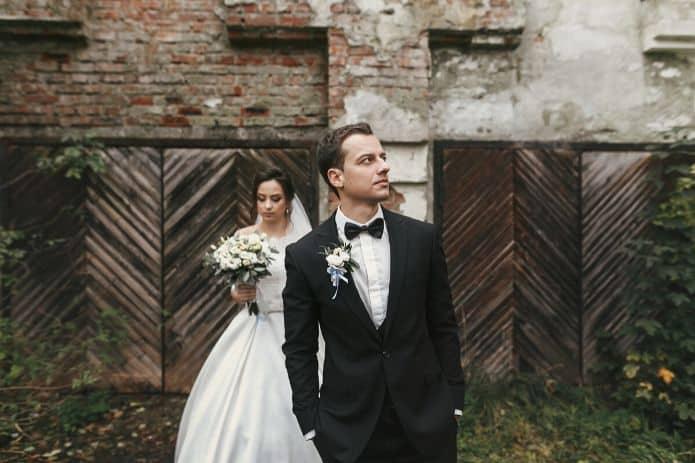 homme en costume de mariage devant une mariée