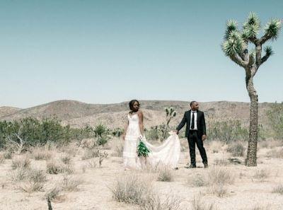 couple de marié dans le désert se tenant la main