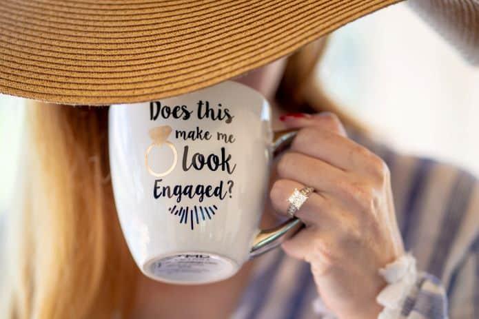 annonce de mariage sur un mug tenue par une femme avec chapeau et bague de fiançailles