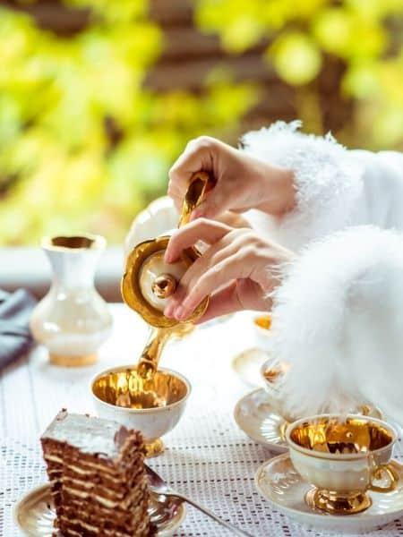 mariée versant du thé dans une tasse à une table
