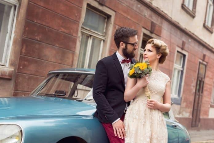 couple de mariés près d'une voiture pendant un mariage thème vintage