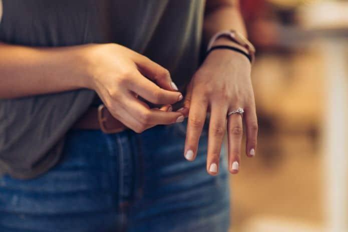 mains d'une femme portant un bague de fiançailles