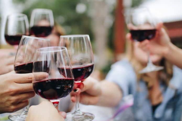amis trinquant avec des verres de vin rouge