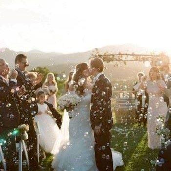 couple de mariés s'embrassant entourés de bulles