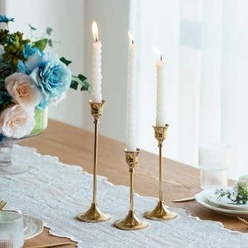 3 chandeliers dorées sur une table