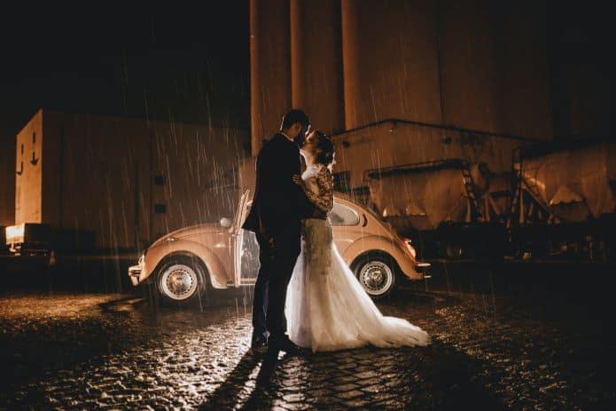 couple de mariés détendu devant une voiture sous la pluie