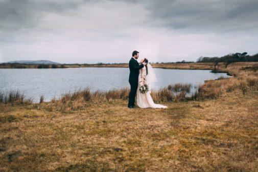 couple de mariés devant un lac