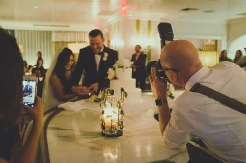 photographe prenant une photo des mariés pendant un mariage