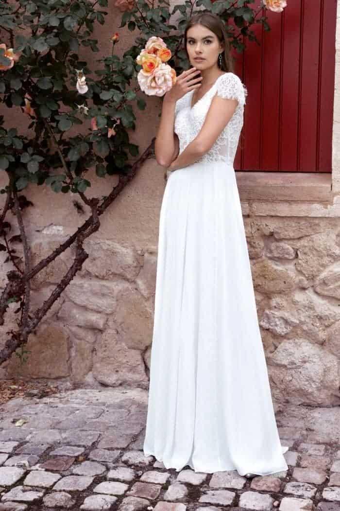 femme portant une robe de mariée forme empire, un bouquet et une couronne de fleur