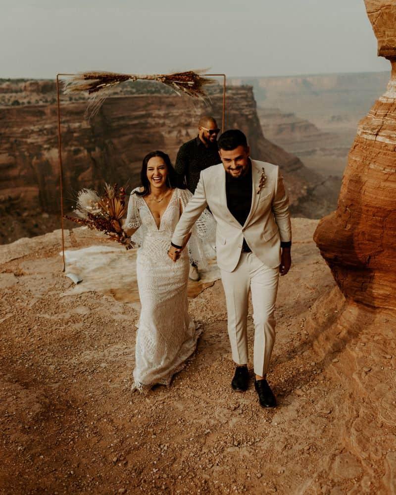 couple de mariés et officiant de cérémonie laique dans le désert