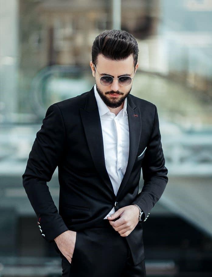 homme invité à un mariage portant un costume noir sans cravate