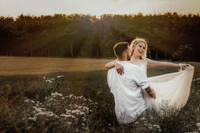 couple dansant dans un champs pendant leur congés de mariage