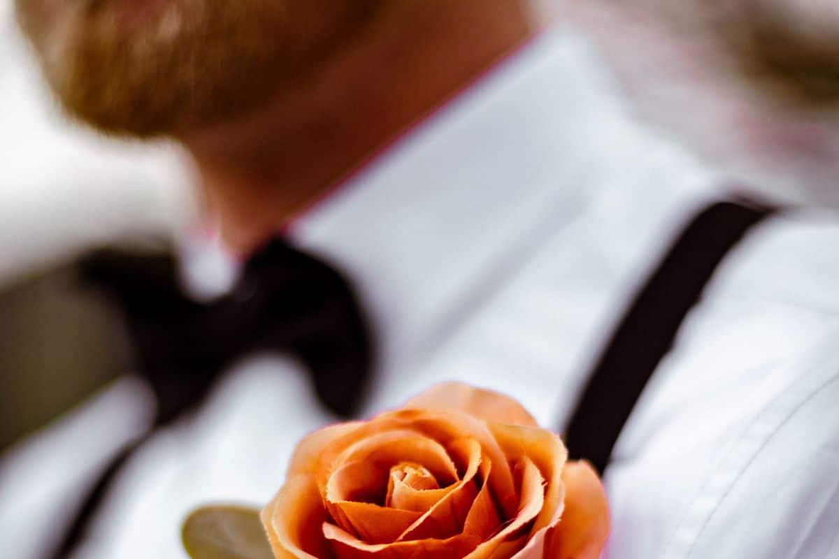 homme portant un smoking pour son mariage avec une rose orange